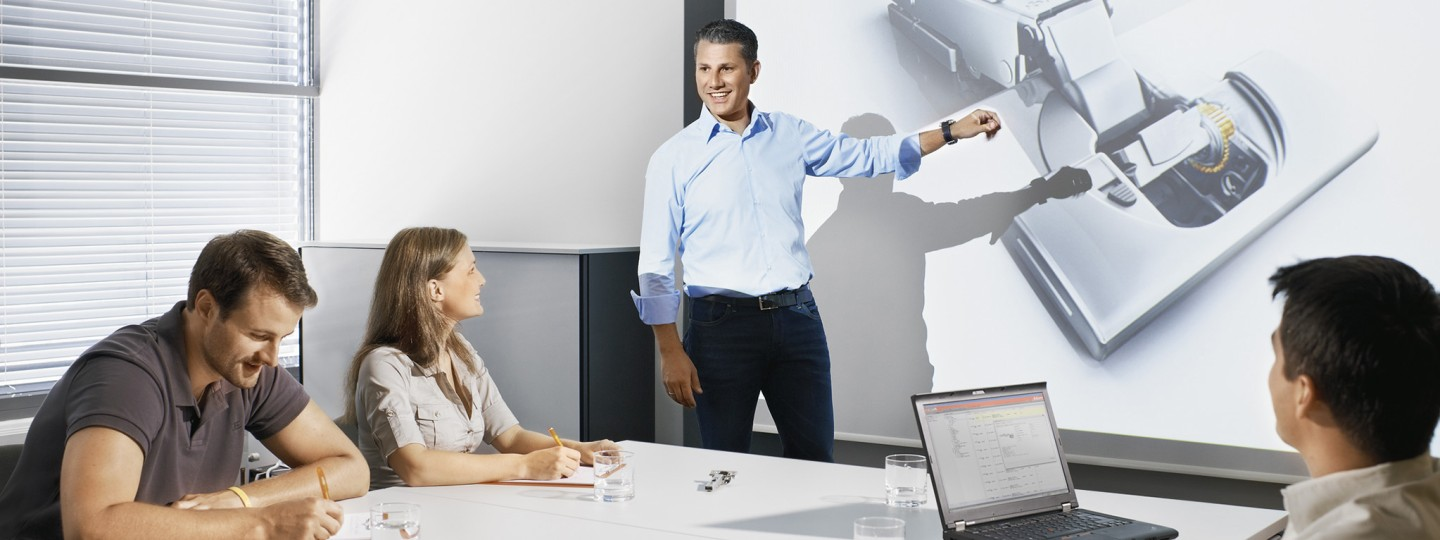 Man presenting Blum Hinge infront of group of people in boardroom